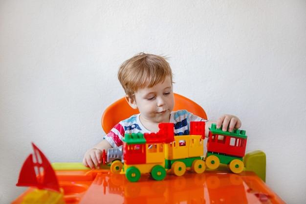 Een kleine blonde jongen zit thuis aan een oranje kindertafel en speelt een kleurrijke plastic bouwdoos. hoge kwaliteit foto