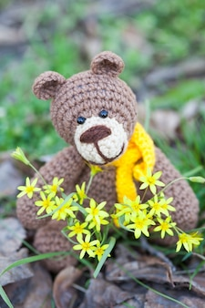 Een kleine bruine beer met een gele sjaal. gebreide speelgoed, handgemaakte, amigurumi