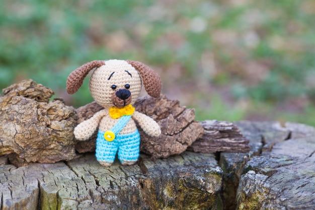 Een kleine bruine hond in blauwe broek. gebreide speelgoed, handgemaakte, amigurumi