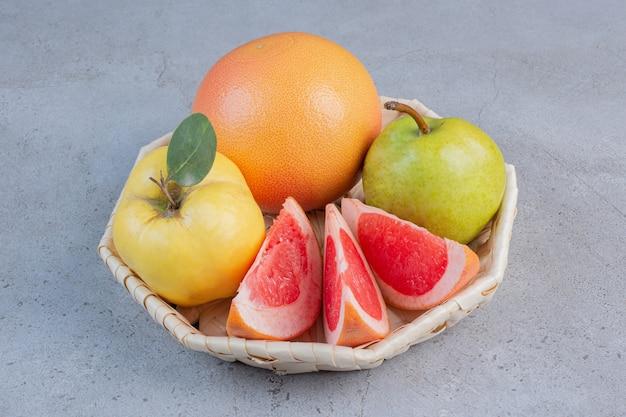 Een kleine bundel fruit in een witte mand op marmeren achtergrond.