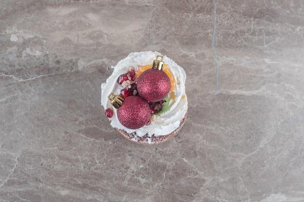 Een kleine cake en kerstballen op marmeren ondergrond