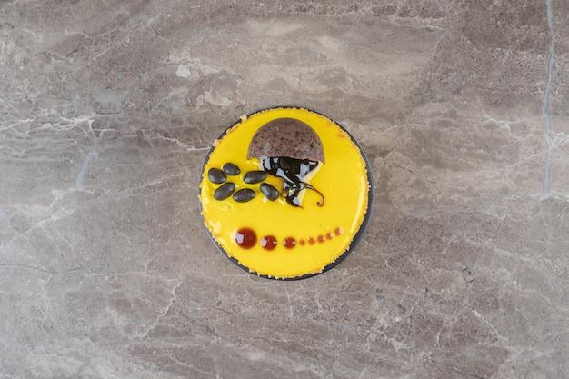 Een kleine cake met een coating met citroensmaak op een marmeren oppervlak