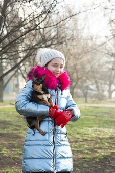 Een kleine chihuahua ligt in de armen van zijn baasje. schoolkind in winterkleren op straat.