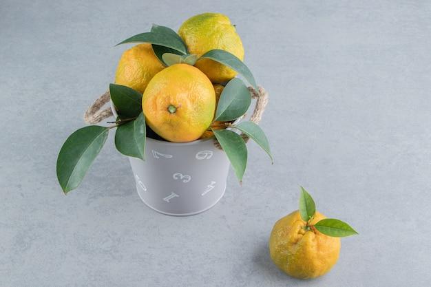 Een kleine emmer vol mandarijnen op marmer.