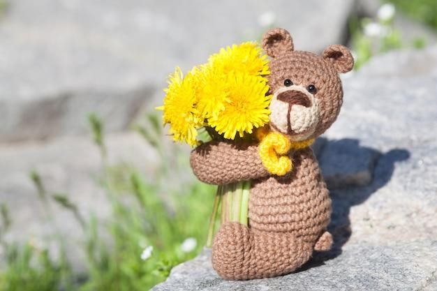 Een kleine gebreide bruine beer met een gele sjaal in de zomertuin. gebreide speelgoed, handgemaakte, amigurumi