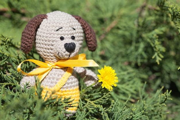 Een kleine gebreide bruine hond met een geel lint in de zomertuin. gebreide speelgoed, handgemaakte, amigurumi
