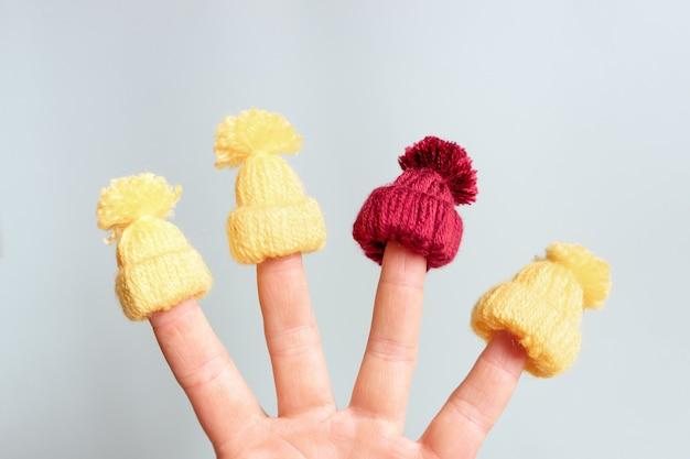 Een kleine gebreide muts wordt op de vingers gezet. het concept van winter, warme kleding en kerstvakantie.