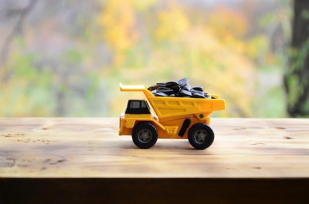 Een kleine gele speelgoedauto is geladen met zonnebloempitten.