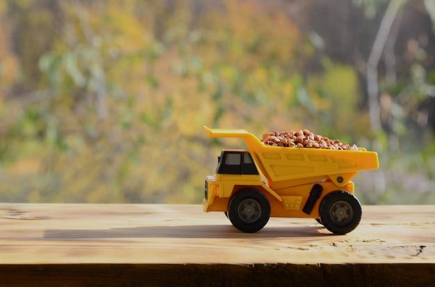 Een kleine gele speelgoedvrachtwagen is geladen met bruine boekweitkorrels