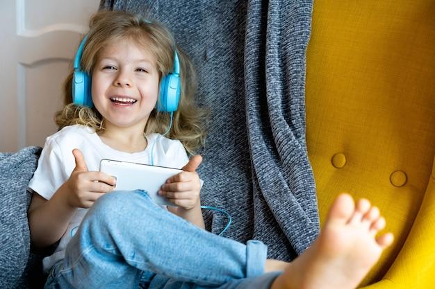 Een kleine gelukkige blonde thuis in een stoel die naar muziek luistert met een koptelefoon en speelt
