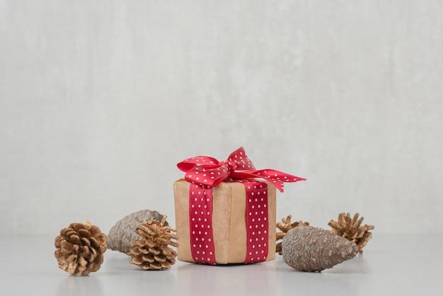 Een kleine geschenkdoos met rode strik en veel dennenappels op een witte muur