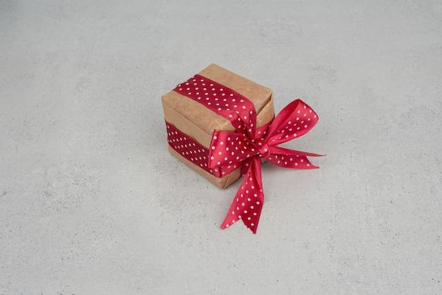 Een kleine geschenkdoos met rode strik op witte achtergrond.