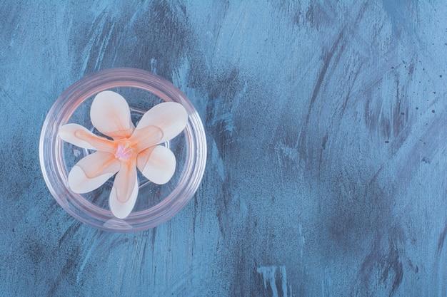 Een kleine glazen schaal met water en roze bloem.