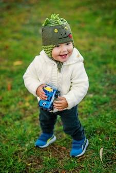 Een kleine glimlachende jongen met twee tanden in warme kleren spelen met speelgoedauto op groen gras op de zonsondergang. gelukkig jeugdconcept.