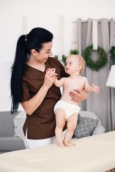 Een kleine grappige baby die massage met professionele vrouwelijke masseuse heeft. kindermassage op de bank in een moderne, gezellige kamer. vriendelijke en vriendelijke kinderarts.