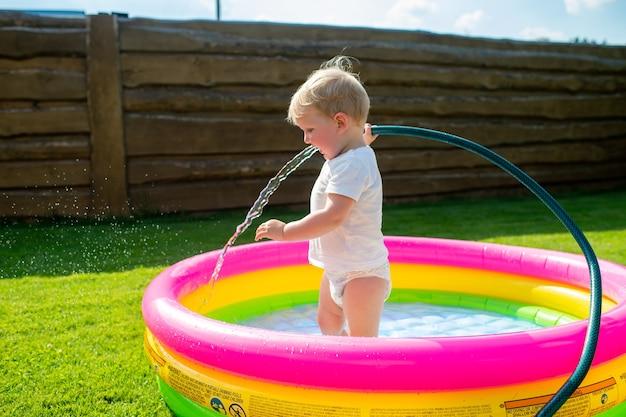 Een kleine grappige jongen die water verzamelt in het kinderzwembad