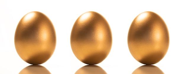 Een kleine groep gouden eieren op een witte achtergrond.
