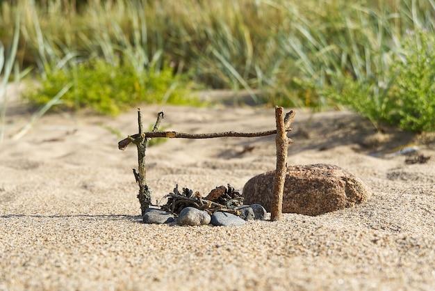 Een kleine handgemaakte open haard op het zandstrand van de oostzee in zonnige zomerdag.