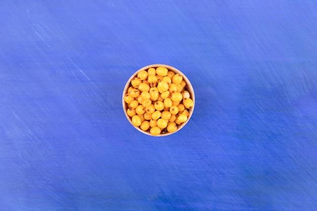 Een kleine houten kom vol gele kersen op blauw oppervlak
