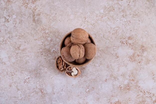 Een kleine houten kom vol gezonde walnoten.