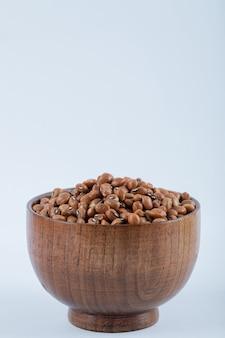 Een kleine houten kom vol rauwe bruine kidneybonen