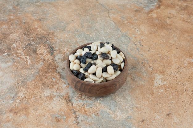 Een kleine houten kom vol rozijnen en noten op marmeren achtergrond
