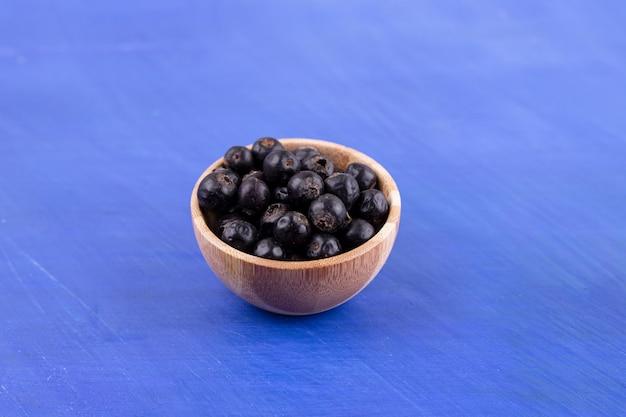 Een kleine houten kom vol zwarte bessen op blauwe ondergrond