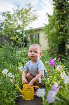 Een kleine hulpjongen zit in de tuin met een gele gieter
