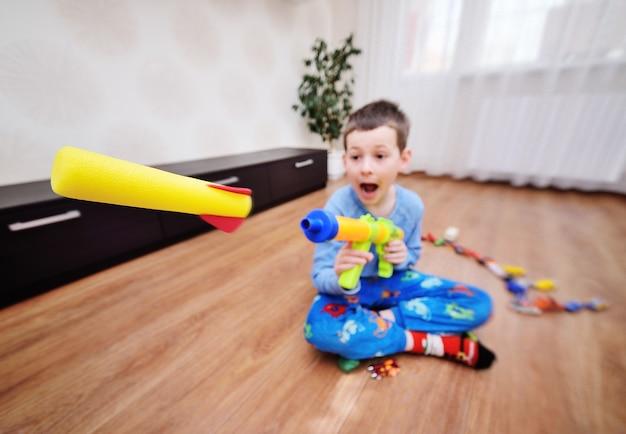 Een kleine, hyperactieve kleuter schiet schuimkogels af met een speelgoedpistool. vlucht van een speelgoedkogel close-up tegen de achtergrond van een lichte kamer.