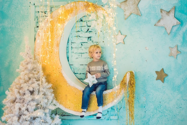Een kleine jongen bereidt zich voor om het nieuwe jaar en kerstmis te vieren. feestelijke kerstversiering