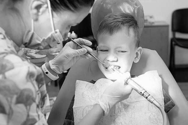 Een kleine jongen bij de receptie van een tandarts in een tandheelkundige kliniek. kindertandheelkunde, kindertandheelkunde. zwart-witte retro-stijlfotografie. mondgezondheid en hygiëne