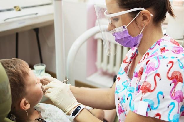 Een kleine jongen bij de receptie van een tandarts in een tandheelkundige kliniek.