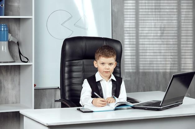 Een kleine jongen die aan het bureau van de kantoordirecteur werkt.