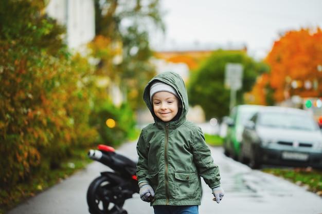 Een kleine jongen die bij de rode motorfiets van zijn kinderen stelt.