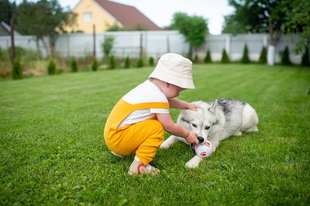 Een kleine jongen die met de hond in de tuin speelt