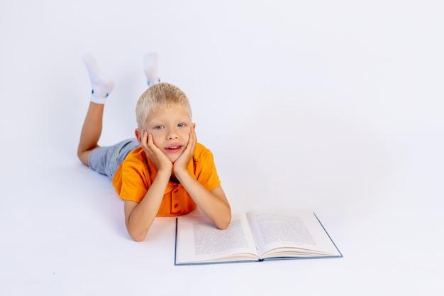 Een kleine jongen die op een witte geïsoleerde achtergrond een boek leest