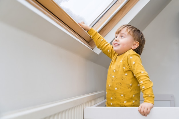 Een kleine jongen die 's ochtends in zijn bed staat en naar het dakraam kijkt.