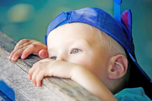 Een kleine jongen die zijn favoriete baseballpet draagt, een hoed die er droevig uitziet en het zat is in het park