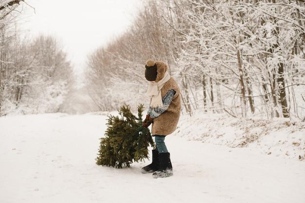 Een kleine jongen draagt een kerstboom in een elfkostuum in een besneeuwd bos. een dwerg in een bontjas sleept een boom langs een besneeuwde weg