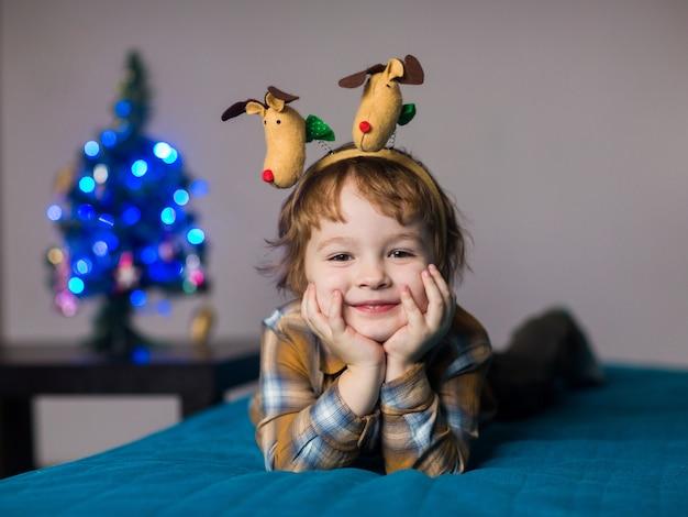 Een kleine jongen draagt kerstrendieren, het kind is blij om kerstmis en nieuwjaar te vieren