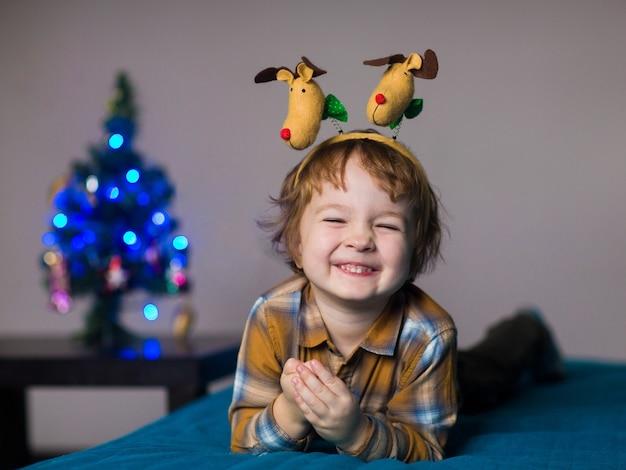 Een kleine jongen draagt kerstrendieren, het kind is blij om kerstmis te vieren