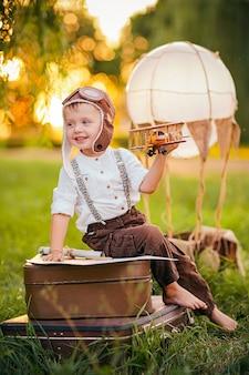 Een kleine jongen droomt ervan om een vintage pilotenpet te worden