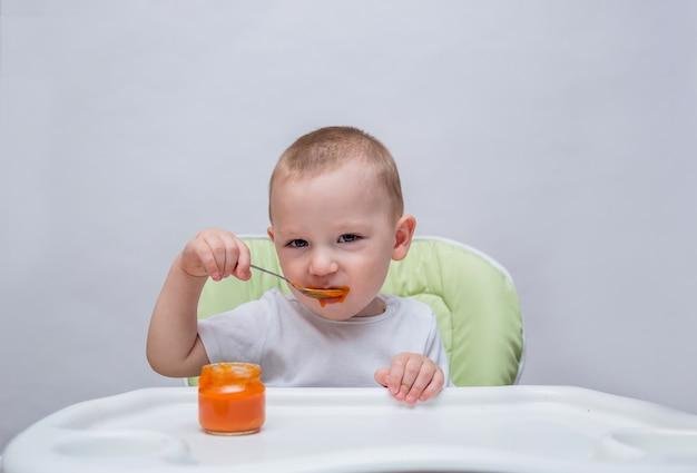 Een kleine jongen eet gepureerde wortelen aan een tafel en kijkt naar de camera op een geïsoleerd wit