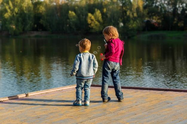 Een kleine jongen en een meisje blazen bellen en staan op een herfstavond op een houten vloer in de buurt van een vijver in een stadspark