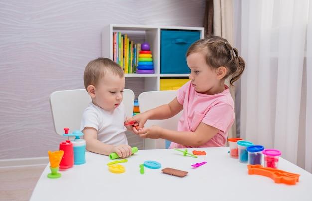 Een kleine jongen en meisje spelen play-doh aan een tafel in de kinderkamer