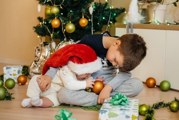 Een kleine jongen en zijn broer spelen met cadeautjes onder een feestelijke kerstboom