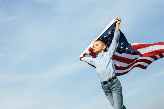 Een kleine jongen houdt een vlag van de verenigde staten tegen de hemel. 4 juli onafhankelijkheidsdag.