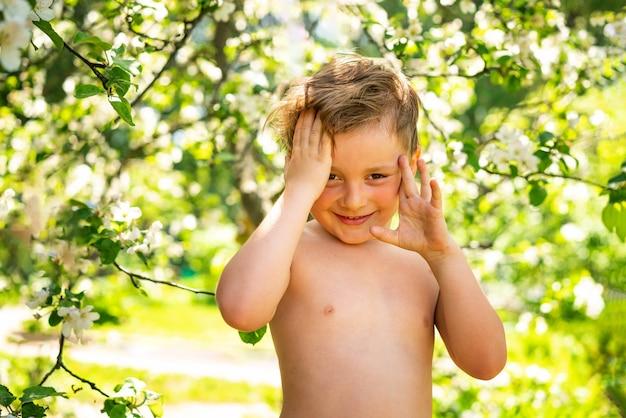 Een kleine jongen in een bloemrijke tuin houdt zijn handen tegen zijn hoofd en glimlacht, staande met zijn blote torso