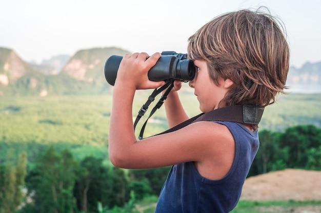 Een kleine jongen in een donker t-shirt van boven kijkt door een verrekijker in de verte naar de natuur.