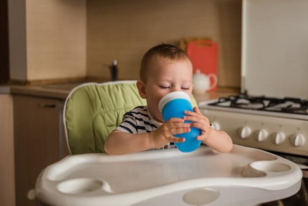 Een kleine jongen in een gestreept t-shirt zit op een hoge stoel en drinkt water uit een fles.